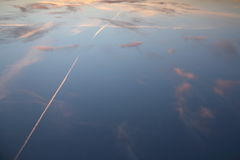 Ίχνη αεροπλάνων σε ένα ανάποδο ηλιοβασίλεμα Στοκ Φωτογραφίες