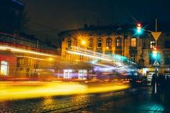 Ίχνη αυτοκινήτων νύχτας Lviv στο εκλεκτής ποιότητας υπόβαθρο οικοδόμησης στοκ εικόνες