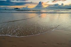 Ίχνη στην άμμο στην άκρη της παραλίας και του ηλιοβασιλέματος Στοκ Εικόνες
