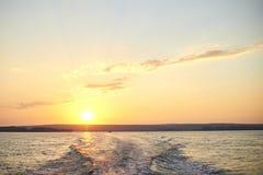 Ίχνος από μια βάρκα στον ποταμό στο ηλιοβασίλεμα Στοκ Φωτογραφία