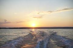 Ίχνος από μια βάρκα στον ποταμό στο ηλιοβασίλεμα Στοκ Εικόνα