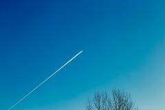 Ίχνος από το αεροπλάνο σε έναν μπλε ηλιόλουστο ουρανό Στοκ φωτογραφία με δικαίωμα ελεύθερης χρήσης