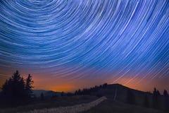 Ίχνος αστεριών πέρα από το βουνό και τραχύ τοπίο με το σταυρό μετεωριτών στοκ φωτογραφία με δικαίωμα ελεύθερης χρήσης