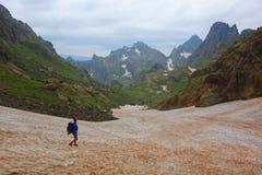 Ίχνος πεζοπορίας με έναν νεαρό άνδρα σε ένα χιονώδες πέρασμα βουνών Tobavarchkhili στα βουνά Καύκασου στη Γεωργία σε ένα πεζοπορώ στοκ φωτογραφία