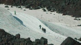 Ίχνος φλόγας τουριστών τυχοδιωκτών alpinsts στη χιονώδη βουνοπλαγιά βουνών ύψους φιλμ μικρού μήκους