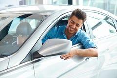 Αίθουσα εκθέσεως αυτοκινήτων Ευτυχές άτομο μέσα στο αυτοκίνητο του ονείρου του Στοκ Φωτογραφία