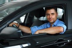 Αίθουσα εκθέσεως αυτοκινήτων Ευτυχές άτομο μέσα στο αυτοκίνητο του ονείρου του Στοκ Εικόνες