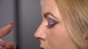 Αίθουσα ομορφιάς Νέα όμορφη πρότυπη συνεδρίαση κοριτσιών στην προεδρία Ο καλλιτέχνης Makeup κάνει makeup τα κορίτσια Ξανθός σε μι απόθεμα βίντεο