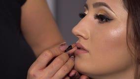 Αίθουσα ομορφιάς Το νέο όμορφο πρότυπο κοριτσιών κάθεται στην προεδρία Ο καλλιτέχνης Makeup κάνει το κορίτσι makeup Brunette σε μ φιλμ μικρού μήκους