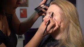 Αίθουσα ομορφιάς Το νέο όμορφο πρότυπο κοριτσιών κάθεται στην προεδρία Ο καλλιτέχνης Makeup κάνει το κορίτσι makeup Καλλιτέχνης M απόθεμα βίντεο
