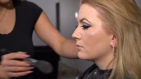 Αίθουσα ομορφιάς Το νέο όμορφο πρότυπο κοριτσιών κάθεται στην προεδρία Ο καλλιτέχνης Makeup κάνει το κορίτσι makeup Ξανθός σε μια απόθεμα βίντεο