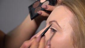 Αίθουσα ομορφιάς Το νέο όμορφο πρότυπο κοριτσιών κάθεται στην προεδρία Ο καλλιτέχνης Makeup κάνει το κορίτσι makeup Καλλιτέχνης M φιλμ μικρού μήκους