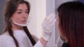 Αίθουσα ομορφιάς Το Beautician σε ένα άσπρη παλτό, μια μάσκα και τα γάντια αξιολογεί τα φρύδια του πελάτη Τα κορίτσια προετοιμάζο φιλμ μικρού μήκους