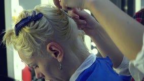 Αίθουσα ομορφιάς barbra Ο κομμωτής στιλίστων κόβει το νέο κορίτσι τρίχας Ο στιλίστας χρησιμοποιεί το ψαλίδι και μια χτένα Κινηματ φιλμ μικρού μήκους