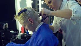Αίθουσα ομορφιάς barbra Ο κομμωτής στιλίστων κόβει το νέο κορίτσι τρίχας Ο στιλίστας χρησιμοποιεί μια ηλεκτρική ξυριστική μηχανή  απόθεμα βίντεο