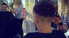Αίθουσα ομορφιάς barbra Ο στιλίστας κάνει το κούρεμα σε έναν νέο όμορφο τύπο Ο τύπος κάθεται σε μια καρέκλα και κοιτάζει απόθεμα βίντεο