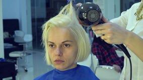 Αίθουσα ομορφιάς barbra Ο στιλίστας ξεραίνει την τρίχα στον πελάτη του Ο κομμωτής κάνει την τρίχα προσδιορισμού Κινηματογράφηση σ απόθεμα βίντεο