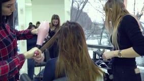 Αίθουσα ομορφιάς barbra Ο στιλίστας ξεραίνει την τρίχα του πελάτη του Ο μαθητής βοηθά τις συμπεριφορές α στιλίστων στιλίστων απόθεμα βίντεο