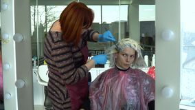 Αίθουσα ομορφιάς barbra Ο στιλίστας χρωματίζει την τρίχα του πελάτη του Το κορίτσι κάθεται σε μια καρέκλα μπροστά από έναν καθρέφ φιλμ μικρού μήκους