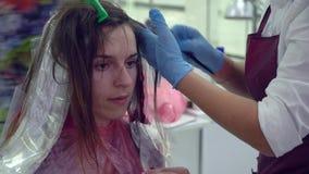 Αίθουσα ομορφιάς barbra Ο στιλίστας χρωματίζει την τρίχα του πελάτη του Το κορίτσι κάθεται σε μια καρέκλα μπροστά από έναν καθρέφ απόθεμα βίντεο