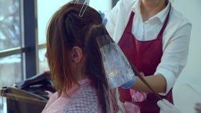 Αίθουσα ομορφιάς barbra Ο στιλίστας χρωματίζει την τρίχα του πελάτη του Ο μαθητής βοηθά τις συμπεριφορές α στιλίστων στιλίστων απόθεμα βίντεο
