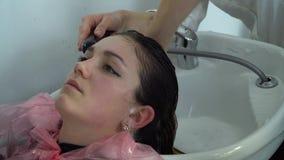 Αίθουσα ομορφιάς barbra Πλύσιμο κοριτσιών η τρίχα τους στον κομμωτή Το κορίτσι χαλαρώνει απόθεμα βίντεο