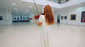 Αίθουσα στοών με έναν φορέα βιολιών σε ένα άσπρο φόρεμα απόθεμα βίντεο