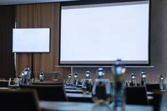 Αίθουσα συνδιαλέξεων με δύο κενές άσπρες οθόνες Μπουκάλια από την εστίαση ελεύθερη απεικόνιση δικαιώματος