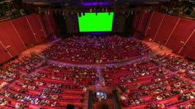 Αίθουσα συνεδριάσεων κινηματογραφικών αιθουσών κινηματογράφων με τους θεατές, τις κόκκινες καρέκλες και την πράσινη οθόνη προβολή απόθεμα βίντεο
