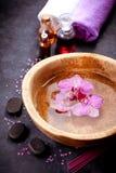 αίσθημα της ειρηνικής καθορισμένης SPA χαλάρωσης Η ορχιδέα ανθίζει σε ένα κύπελλο με το νερό, zen πέτρες και πετρέλαια μασάζ Στοκ Φωτογραφίες