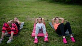 Αίσθημα των κοριτσιών ABS σας Ομάδα αθλητικών νέων sportswear που κάνει τις σωματικές ασκήσεις στην πράσινη χλόη το καλοκαίρι φιλμ μικρού μήκους