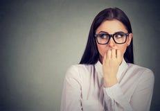 Αβέβαιη ανήσυχη γυναίκα που δαγκώνει τα νύχια της που ποθούν για κάτι στοκ εικόνα