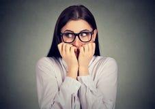 Αβέβαιη ανήσυχη γυναίκα που δαγκώνει τα νύχια της που ποθούν για κάτι στοκ φωτογραφία