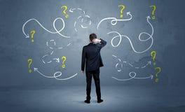 Αβέβαιος επιχειρηματίας με τα ερωτηματικά στοκ εικόνες