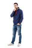Αβέβαιος σοβαρός νεαρός άνδρας στην μπλε μπλούζα που εξετάζει τη κάμερα skeptically Στοκ Εικόνες