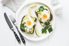 Αβοκάντο και αυγό σε ολόκληρη τη φρυγανιά σιταριού στο άσπρο πιάτο στοκ εικόνα με δικαίωμα ελεύθερης χρήσης