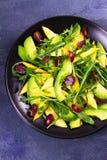 Αβοκάντο, μάγκο, κόκκινο σταφύλι και σαλάτα arugula στο μαύρο πιάτο Στοκ Εικόνες