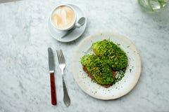 Αβοκάντο στο ψωμί σίκαλης και ένα φλιτζάνι του καφέ Στοκ Φωτογραφία