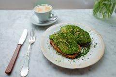 Αβοκάντο στο ψωμί σίκαλης και ένα φλιτζάνι του καφέ Στοκ εικόνα με δικαίωμα ελεύθερης χρήσης