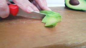 Αβοκάντο φετών χεριών σε ξύλινο φιλμ μικρού μήκους