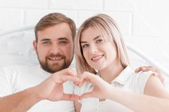 Αγάπη, άνθρωποι και η έννοια της ευτυχίας - το χαμογελώντας ζεύγος στο κρεβάτι, δίνει την παραγωγή μιας μορφής καρδιών Στοκ Φωτογραφίες