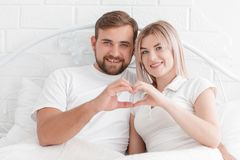 Αγάπη, άνθρωποι και η έννοια της ευτυχίας - το χαμογελώντας ζεύγος στο κρεβάτι, δίνει την παραγωγή μιας μορφής καρδιών Στοκ Φωτογραφία