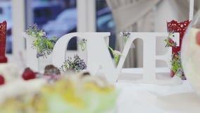 Αγάπη λέξης γαμήλιας τελετής ντεκόρ στην τράπεζα στο υπόβαθρο των λουλουδιών απόθεμα βίντεο