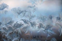 αγάπη λέξης και μια καρδιά στο γυαλί με τα παγωμένα σχέδια στοκ εικόνες με δικαίωμα ελεύθερης χρήσης