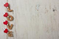 Αγάπη λέξης με τις κόκκινες καρδιές σε ένα άσπρο υπόβαθρο ξύλινο Στοκ Φωτογραφίες