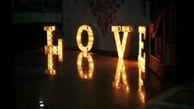 Αγάπη λέξης που αποτελείται από τα φω'τα στο στιλπνό πάτωμα απόθεμα βίντεο