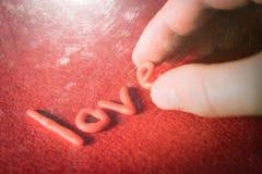 Αγάπη λέξης των διακοσμητικών επιστολών σε ένα κόκκινο υπόβαθρο Στοκ Φωτογραφία