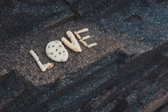 Αγάπη λέξης φιαγμένη από κοχύλια που συλλέγονται σε μια πέτρα γρανίτη Στοκ εικόνες με δικαίωμα ελεύθερης χρήσης