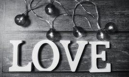Αγάπη λέξης φιαγμένη επάνω από άσπρες ξύλινες επιστολές σε ένα ξύλινο υπόβαθρο Στοκ Εικόνα