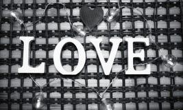 Αγάπη λέξης φιαγμένη επάνω από άσπρες ξύλινες επιστολές σε ένα ξύλινο υπόβαθρο Στοκ Εικόνες